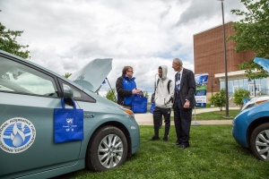Three males speak together at an Odyssey event with a Toyota Prius in the foreground.