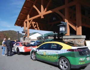 Two cars with marketing decals on display at an event while two men speak in the background.