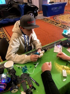 Young man seated at table working on a hydrogen-powered model car.