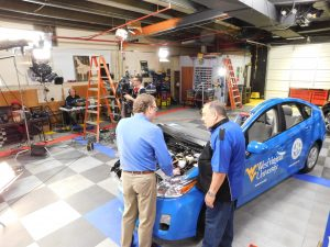 Micheal Smyth (l) explaining electric vehicle maintenance to Pat Gross